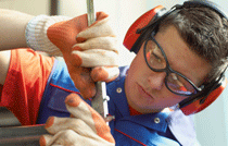 Male Employee with Goggles and Headset Using a Wrench